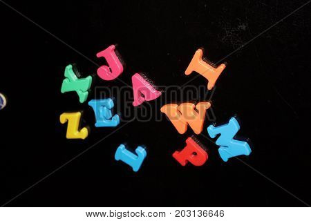 Colored magnet letters on a black refrigerator pink blue orange yellow green