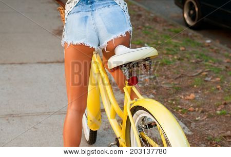 Beautiful woman with bike on street. Bicyclist riding in park.