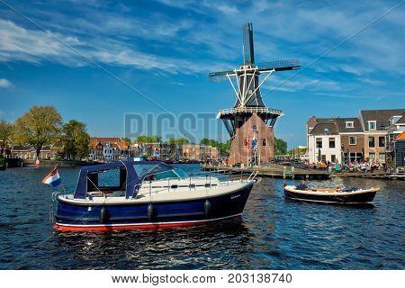 HAARLEM, NETHERLANDS - MAY 6, 2017: Harlem cityscape with windmill De Adriaan on Spaarne river. Haarlem,  Netherlands