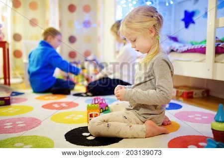 Three Children Playing With Colorful Plastic Blocks At Kids Room. Cute Girl Playing At Home Or Dayca
