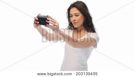 Closeup portrait of pretty young brunette woman in white t-shirt holding retro camera isolated over white background