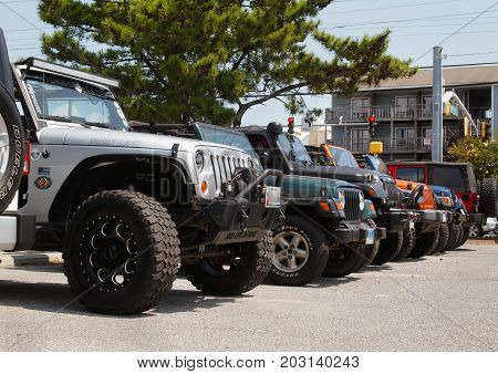 OCEAN CITY MD - AUGUST 26 2017: Closeup on a row of Jeep front ends parked side by side extending into to the background. at Jeep Week 2017 in Ocean City Maryland.
