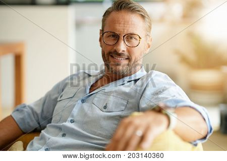Handsome mature man with eyeglasses relaxing in sofa at home