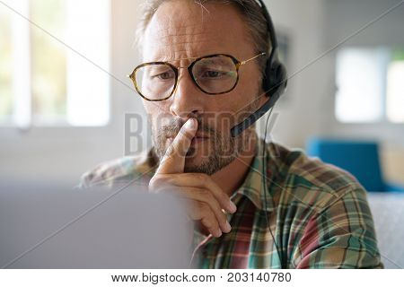 Portrait of man with eyeglasses connected with laptop