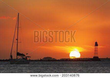 atardecer sol barco yate farola naranja río agua