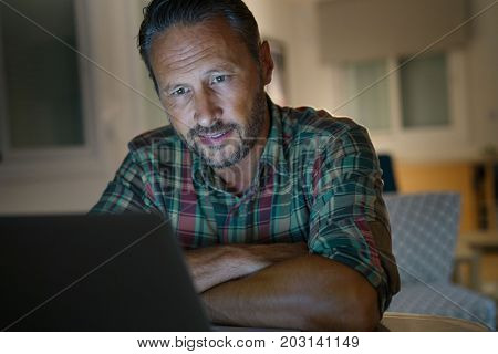 Man at home working late on laptop computer at night