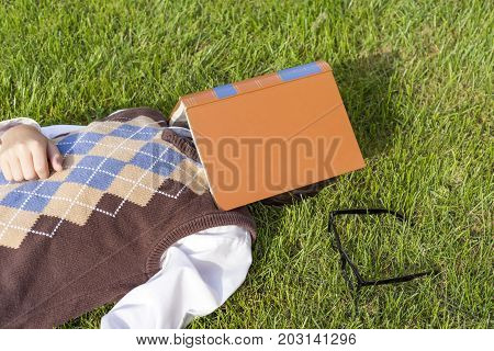 Preteen Boy Wearing Retro Sweater Vest Lying In Grass With Book Over Face, Glasses On Ground