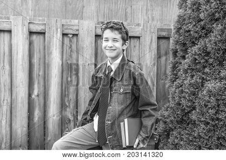 Preteen Boy Wearing Stylish Clothes And Holding Books Ready For School, Posing Near Fence