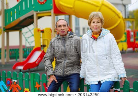 Elderly woman and man near playground at autumn, shallow dof