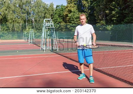 athletic young man in white t-shirt and blue shorts playing tennis on court summer day