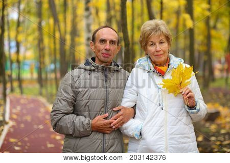 Elderly man and woman in white jacket walk in fall park, shallow dof