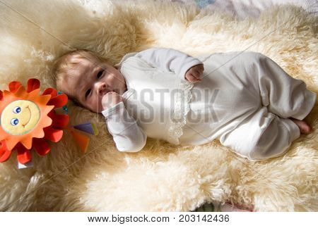 newborn happy sweet baby on furry blanket with toy sun in soft colors