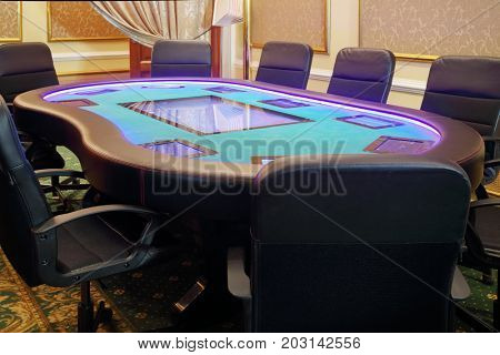 Modern empty hall in casino with electronic poker table and soft armchairs