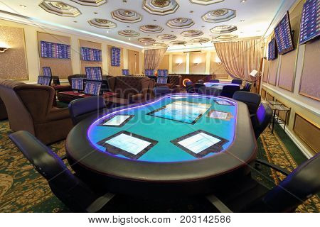 Empty casino with modern electronic poker table and electronic gaming machines, my photo on screens