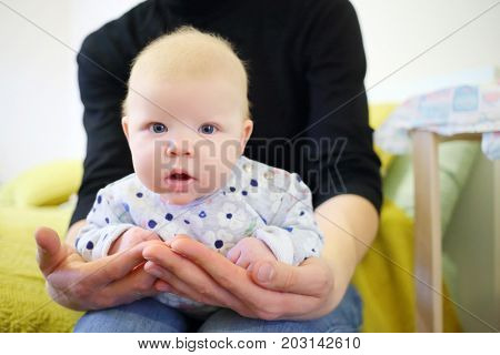 Little funny baby is in hands of father in room, shallow dof