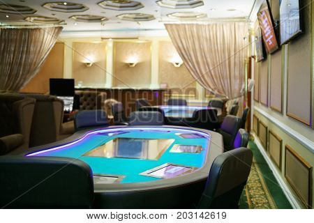 Empty casino with modern electronic poker tables and beautiful curtains