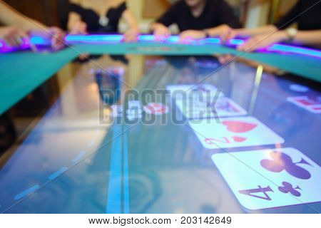 Electronic table in modern casino and hands of four players out of focus
