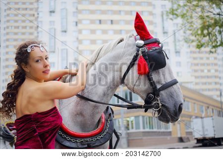 Happy woman in red dress ctrokes horse in harness near residential building