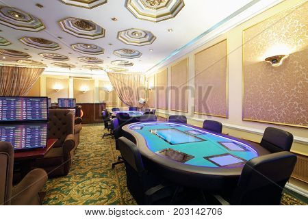 Empty casino with modern electronic poker table and screens on wall, my photo on screens