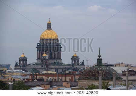 Isaac Cathedral among roofs of buildings, St Petersburg, Russia at evening