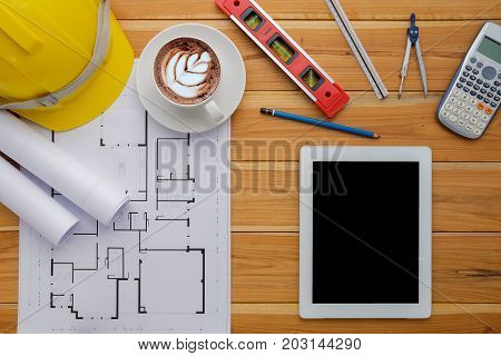 Architect desk project in construction site with blueprintpentablet computerhardhatconstruction level calculator and cup of coffee .Top view with copy space.