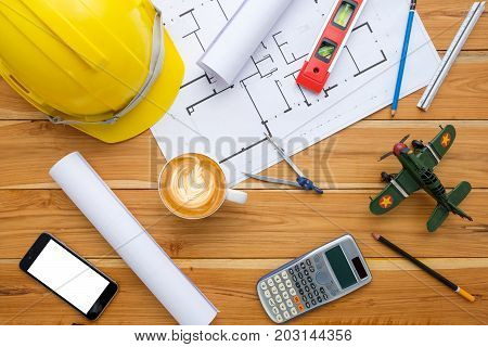 Architect desk project in construction site with blueprintpenblank screen smartphonehardhatconstruction level and calculator.Top view.