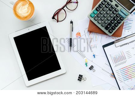 Modern White office desk table with blank screen tablet financial report pen eyeglass and calculator. Top view with copy space.Working desk table concept.