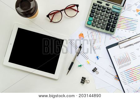 Modern white office workplace top with blank screen tablet pen calculator cup of coffee and chart or graph over backboard. Top view with copy space