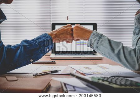 Business team giving fist bump after complete deal. Successful Teamwork Partnership in an Office.Business concept.