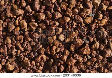 little brown stone on dry ground for brown background