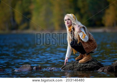 young pretty woman outdoor in fall sitting by the lake