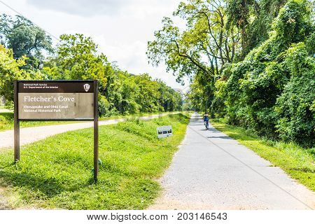 Washington DC USA - August 28 2017: Sign for Fletcher's Cove and Chesapeake and Ohio Canal National Historical Rock Creek Park with woman on Capital Crescent bicycle trail