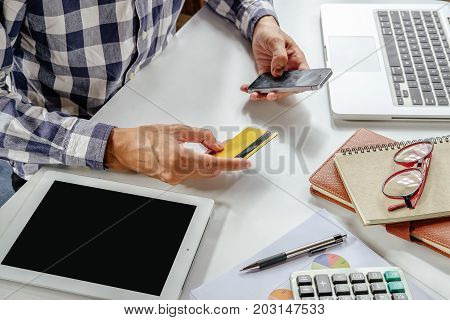 Hipster man hands holding smart phone and using credit card for online shopping.Online shopping concept.