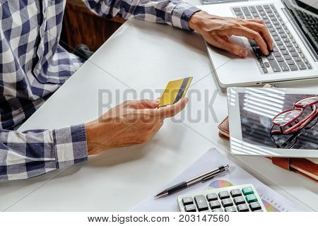 Hipster man hands using laptop and using credit card for online shopping.Online shopping concept.