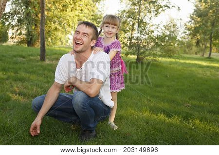 Family. Father and daughter outdoors. Walk in the city park. They laugh and smile. Happiness of paternity