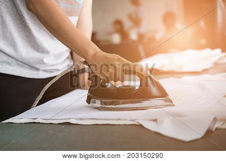 Young Woman Ironing Waterproof Film On Fabric At Shop. Worker Working On Manual Screen Printing On T