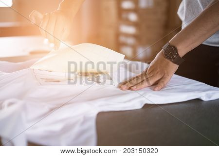 Young Woman Pull Out Paper From Waterproof Film On Fabric At Shop. Worker Working On Manual Screen P