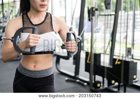 Young Woman Execute Exercise With Machine In Fitness Center. Female Athlete Pump Up Muscle With Cabl