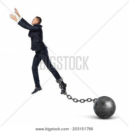 A businessman shackled to a huge iron ball leaps up and tries to catch something above. No boundaries. Break free. Risk and gain.