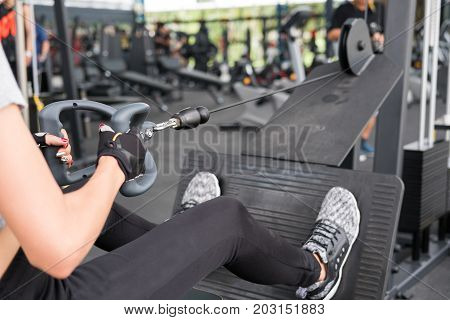 Young Woman Execute Exercise In Fitness Center. Female Athlete Training With Rowing Machine In Gym.