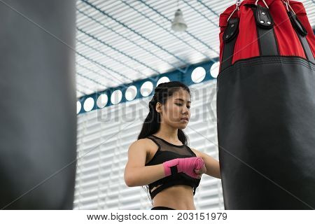 Young Woman Execute Exercise In Fitness Center. Female Athlete Hitting And Punching Sandbag With Row