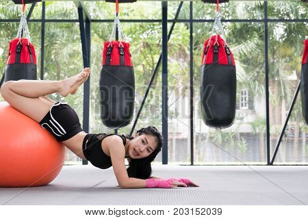 Young Woman Execute Exercise In Fitness Center. Female Athlete Training With Ball In Gym. Sporty Gir