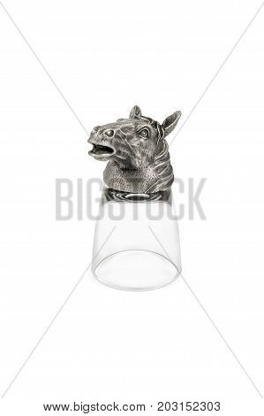 Inverted wineglass for vodka with horse head on the bottom isolated on white background