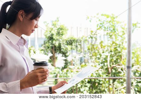 Businesswoman Holding Coffee Cup & Financial Summary Graph Outside Office Building. Beautiful Young
