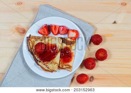 Crepes with fresh ripe strawberries and jam