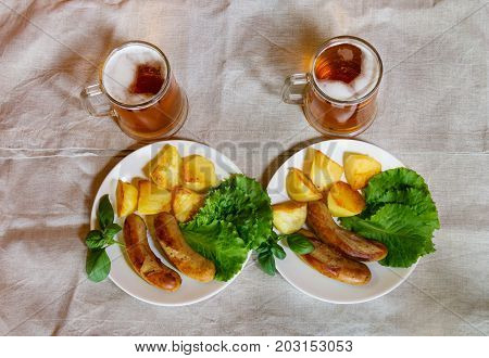 Mugs of beer with plates of grilled sausages. Top view