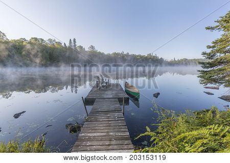 Green Canoe And Dock On A Misty Morning - Ontario, Canada