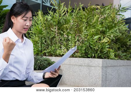 Businesswoman With Financial Graph Sitting Outside Office Building. Young Asian Woman Analyzing Inve