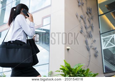 Businesswoman Holding Mobile Phone & Coffee Outside Office Building. Beautiful Young Asian Woman Wit