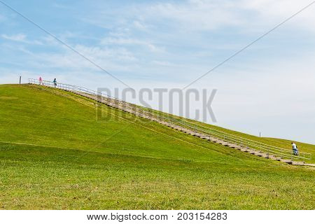 VIRGINIA BEACH, VIRGINIA - JULY 10, 2017:  People exercise on a sunny summer day on the steep stairway at Mount Trashmore Park, the site of a former landfill.